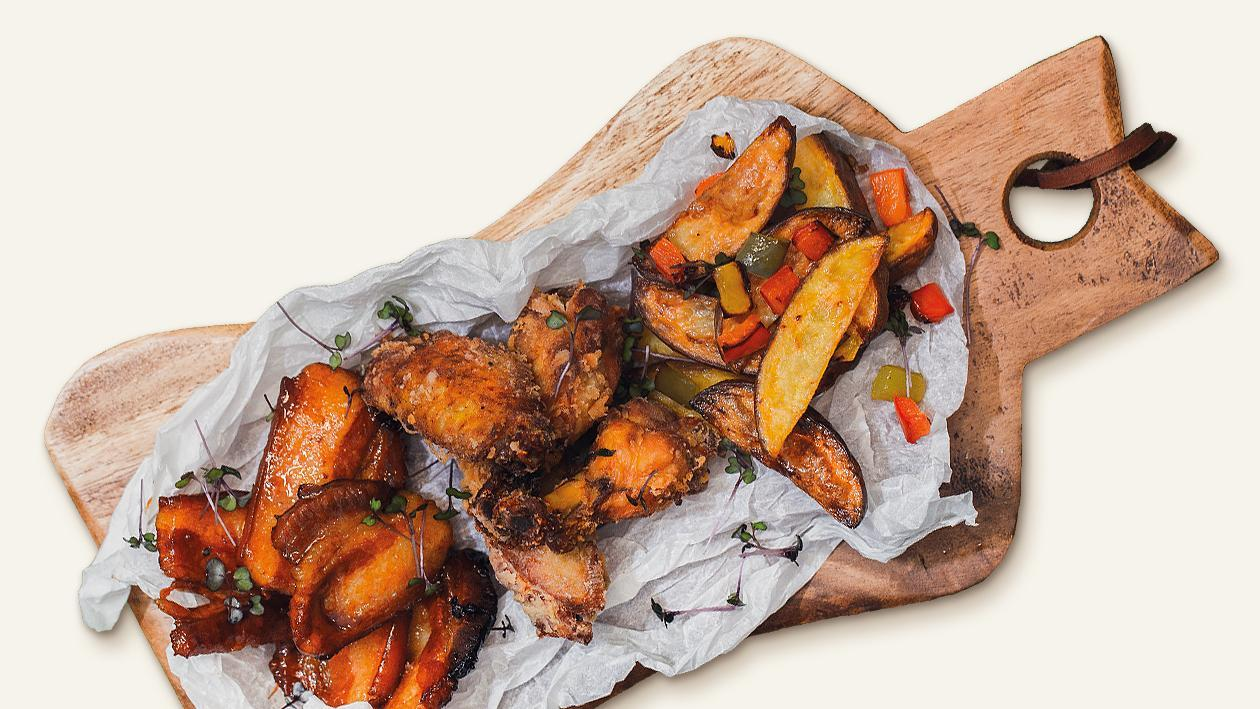 Глазирано свинско месо и хрупкави пилешки крилца с печени картофи