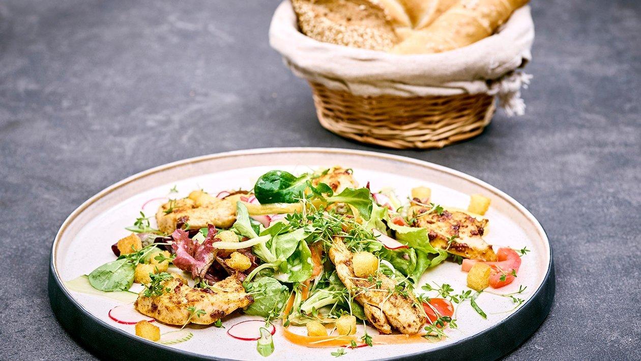 Marinierter Blattsalat mit gegrillten Hühnerbruststreifen,Croutons und klarer Dressing