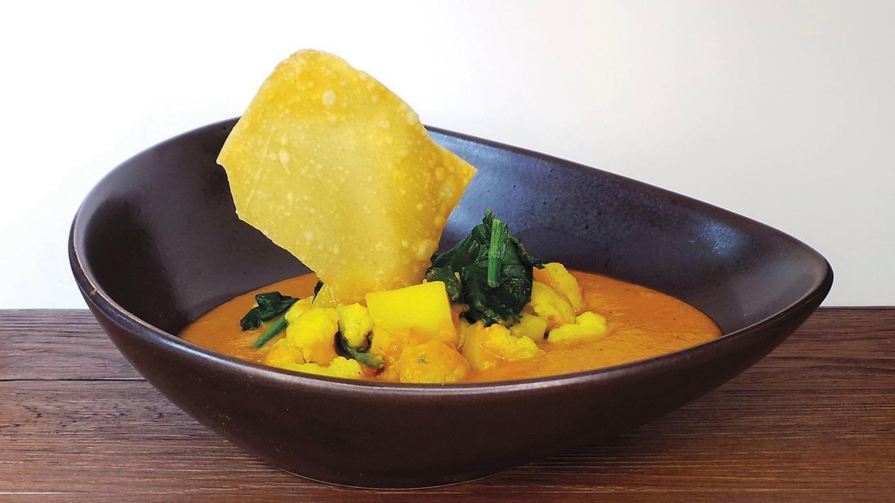Dal von roten Linsen mit Curry-Blumenkohl, Kartoffeln und Spinat dazu gebackene Wan Tan
