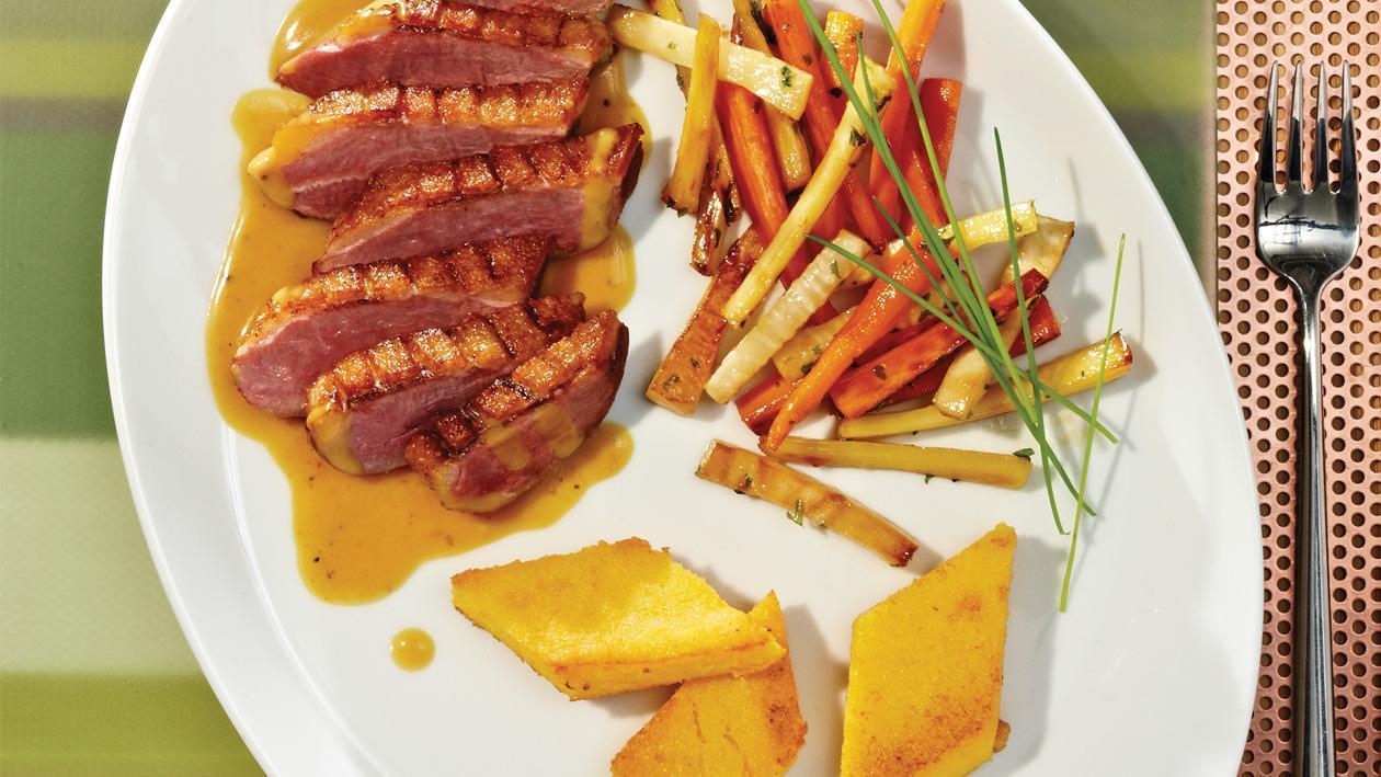 Entenbrust an pfeffriger Curry-Blutorangen-Sauce, glaciertem Wurzelgemüse und Polentaplätzchen