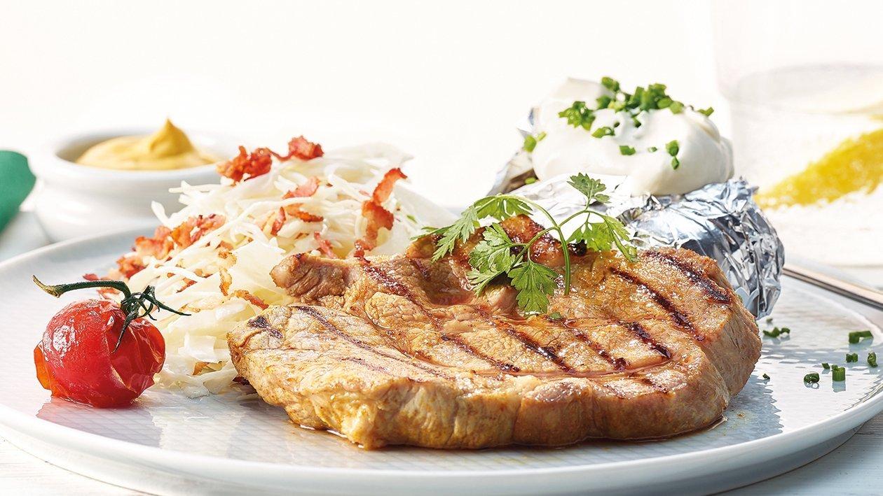 Gegrilltes Schweinenackensteak mit Krautsalat und Ofenkartoffel
