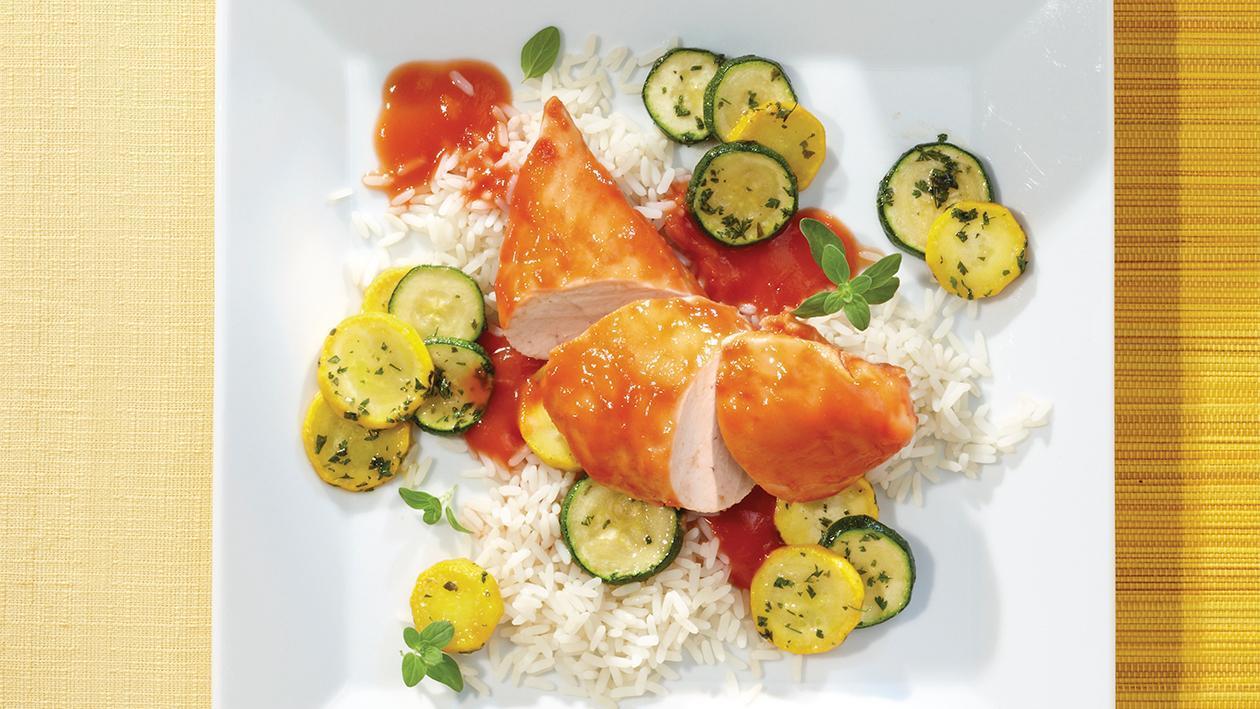 In Tomatensauce pochiertes Hähnchenbrustfilet mit Zucchini-Gemüse und Reis