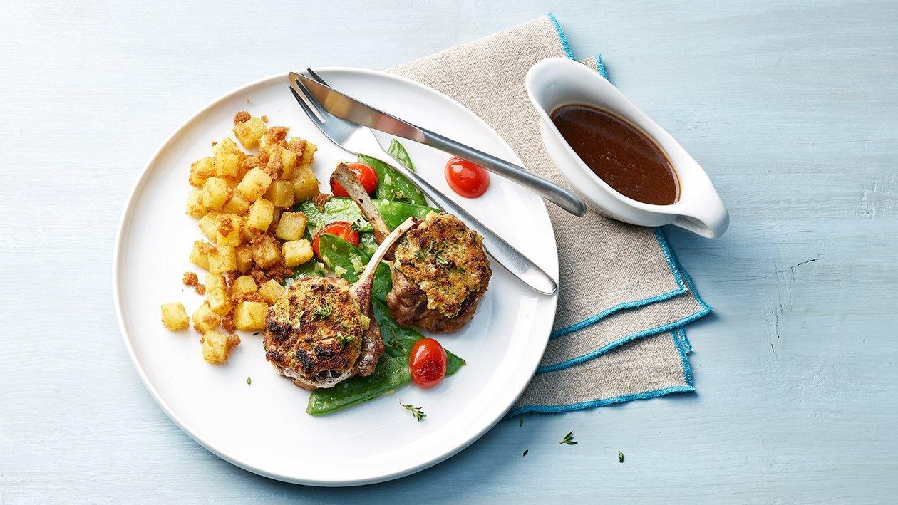 Lammkoteletts mit Knoblauch-Kräuter-Kruste, Zuckerschoten und Sandkartoffeln