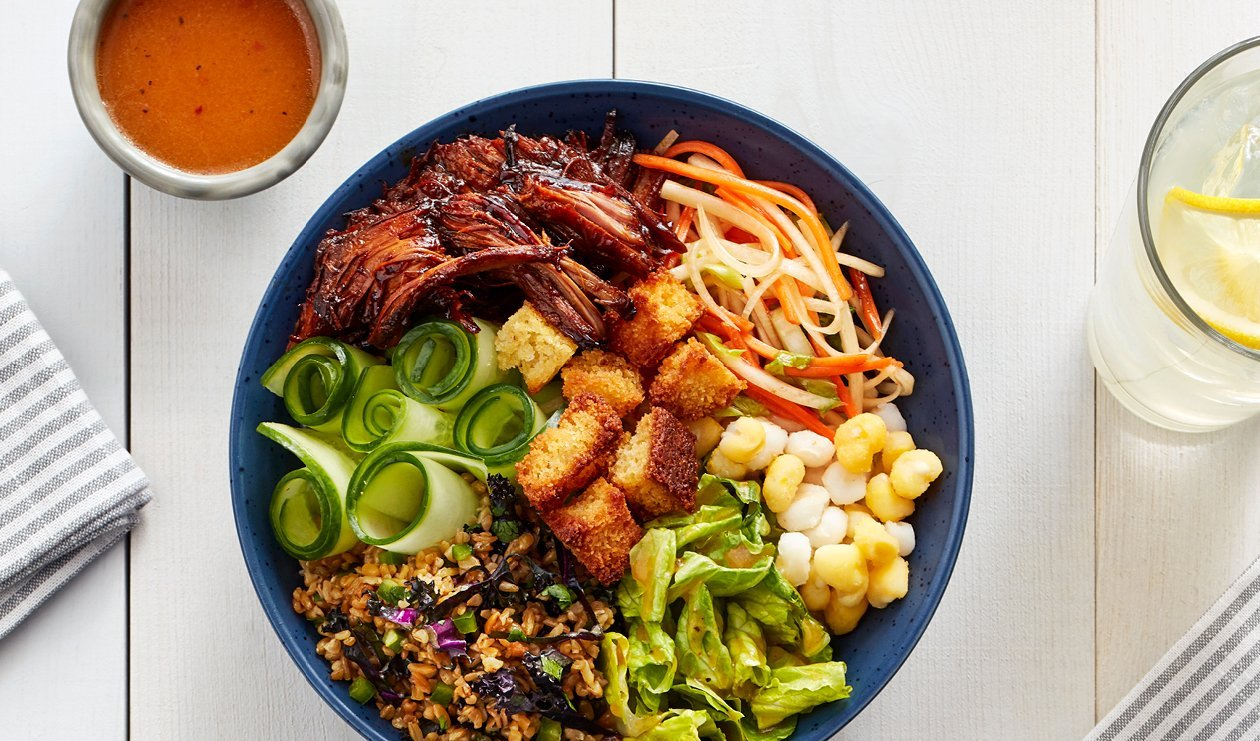 BBQ Pulled Pork Bowl with Hominy, Smoky Peach Kimchi Slaw and Cornbread Croutons – recipe