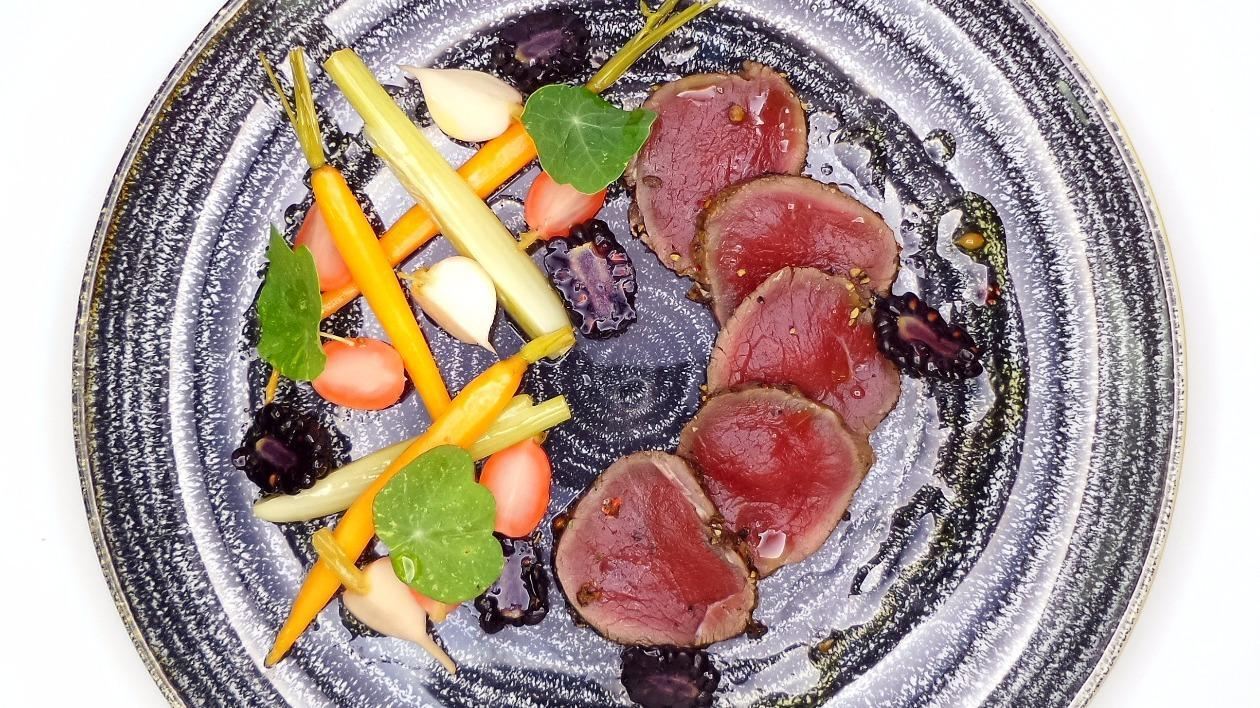 Cured venison with pickled garden vegetables, blackberries and nasturtium leaves