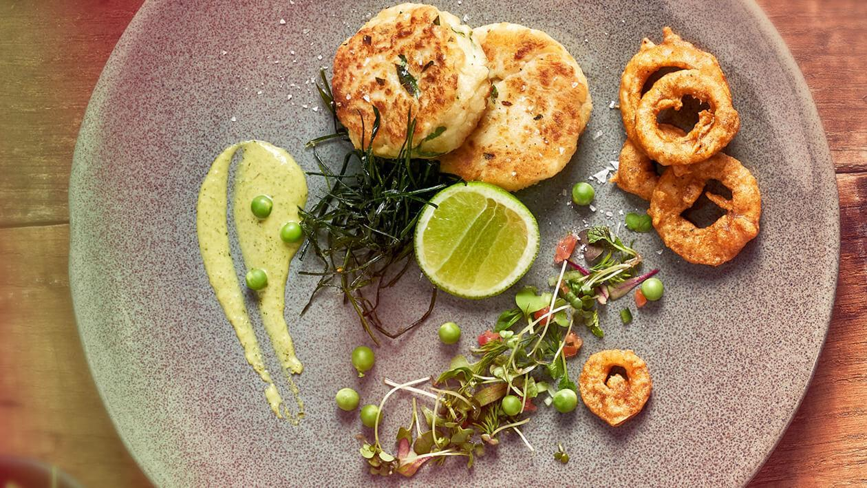 Crunchy Pan-Fry - Fish Cakes with a Garden-Fresh Micro Herb Salad served with Onion Bhajas and Pea Cream