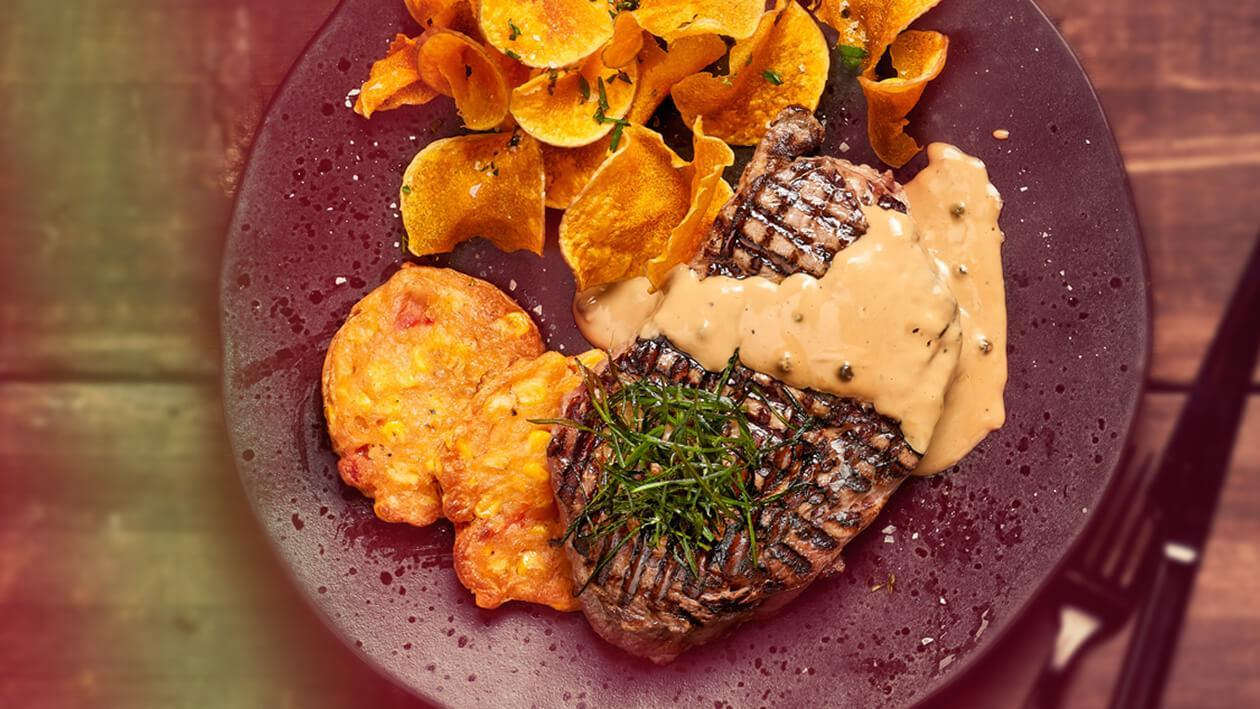 Saucy Corn: Grilled Steak with a Corn and Red Pepper Fritter Served with Crisp Butternut Shavings and Creamed Peppercorn Sauce