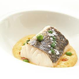 Versión de la merluza a la gallega cocida en fondo de marisco sobre espuma de ajada y guisantes