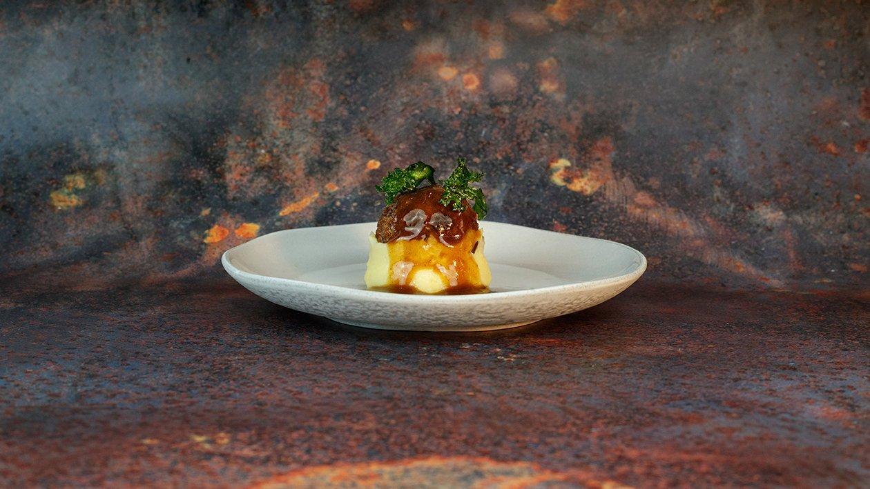 Albóndigas de ternera glaseadas sobre patata cremosa y berza frita