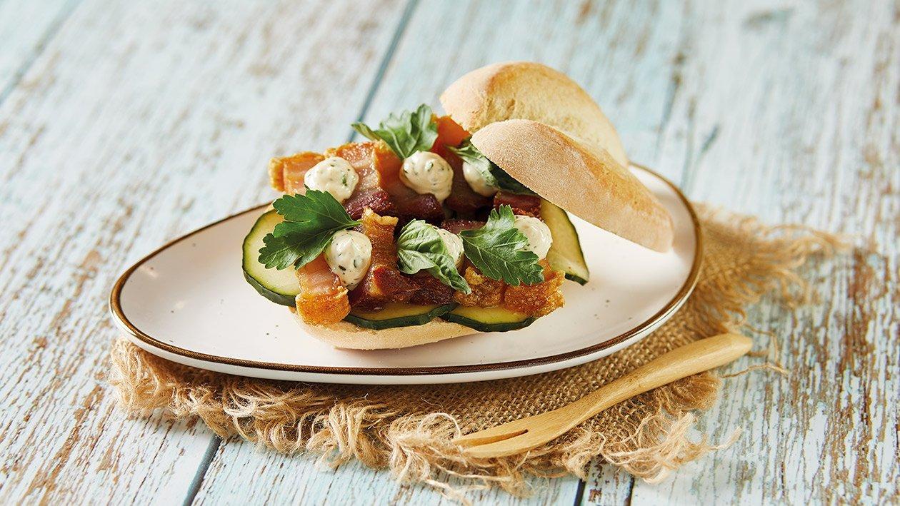 Panecillo crujiente con torrezno, pepino encurtido y mayonesa de cilantro