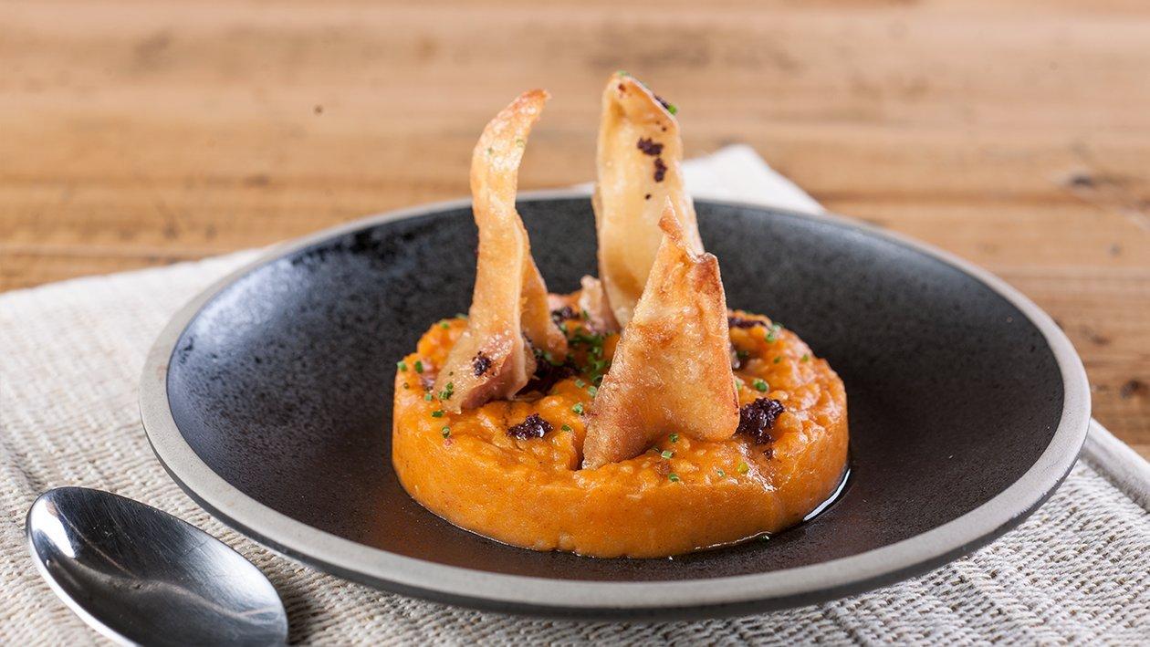 Patatas revolconas con oreja de cochinillo crujiente y tapenade
