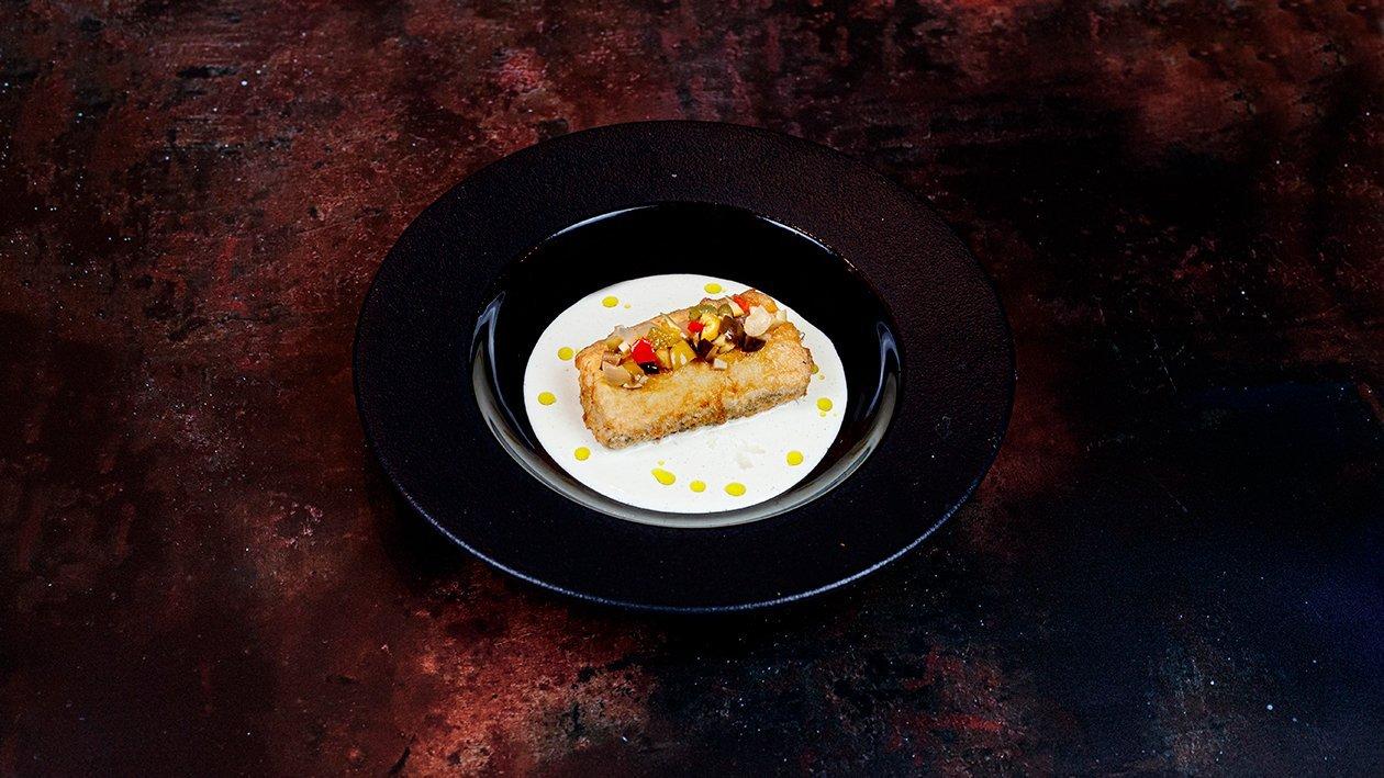 Pescadilla rebozada y frita sobre gazpachuelo y encurtidos