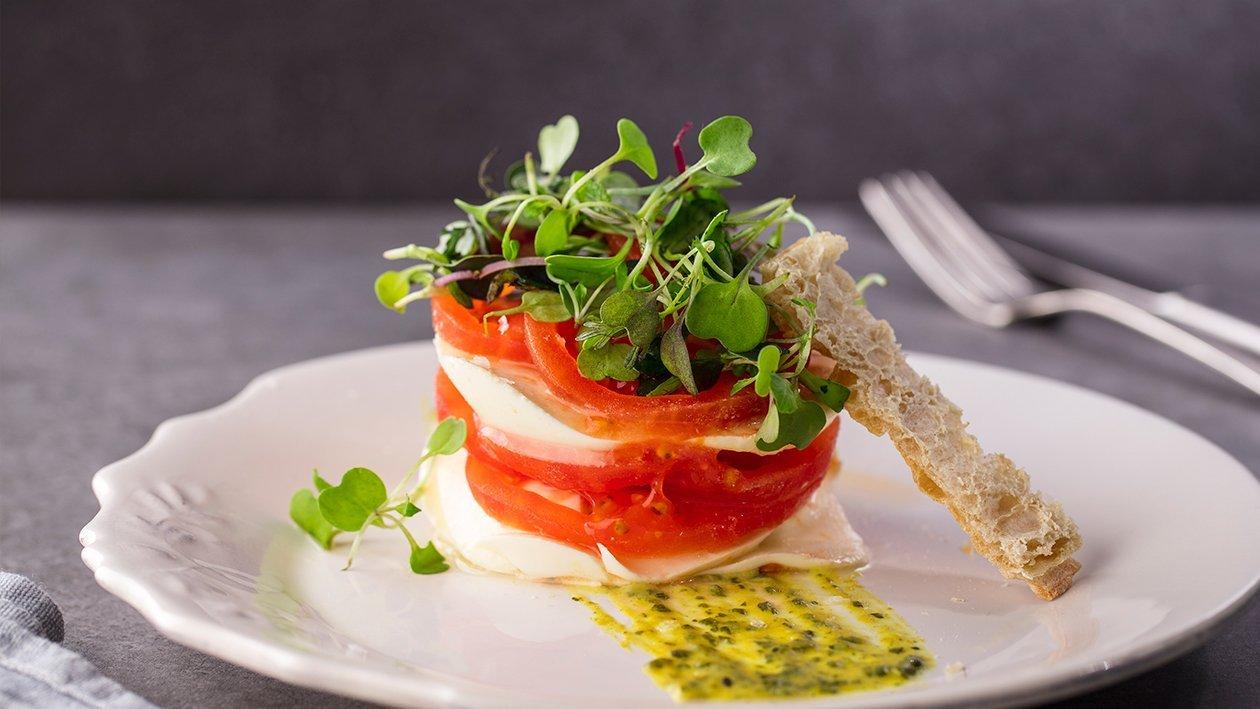 Timbal de tomate y queso fresco crujiente de pan y vinagreta compuesta de mostaza