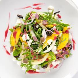 Salade fraîche avec melon, mangue, fêta et dressing framboises