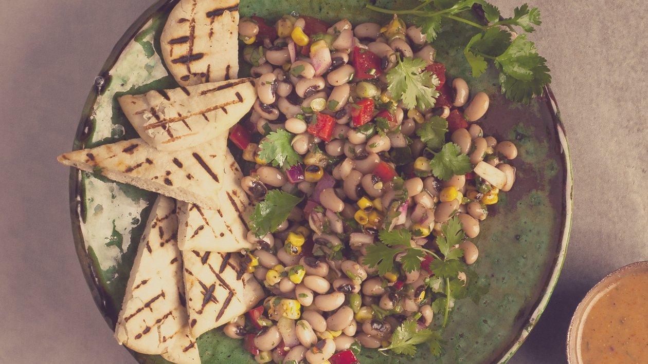Salade de cornilles, pain à pita grillé, oignon rouge et sauce africaine orientale – Recette