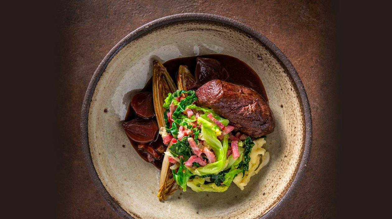 Sanglier avec chou vert, lard, chicon, une mousseline de pommes de terre et une sauce gibier et oignons frits – Recette