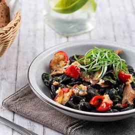 Orecchiette al nero con aringa affumicata, pomodorino gratinato e cipollotti