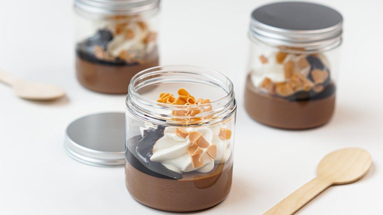 Budino al cioccolato con topping al cacao, chips di caramello e panna montata – Ricetta