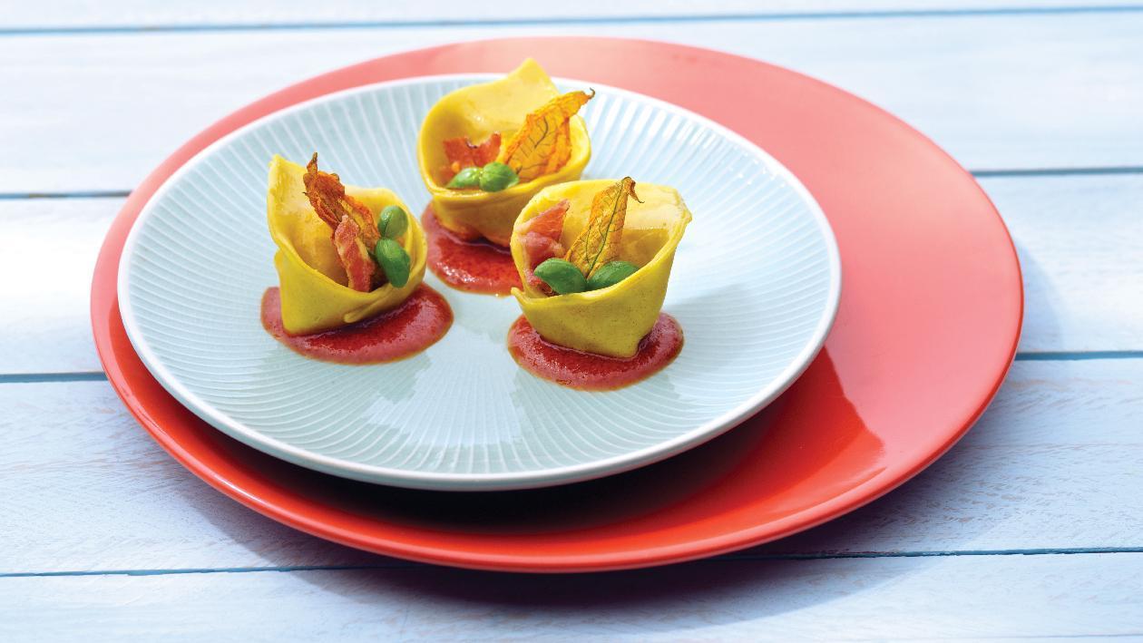 Cappellacci ripieni con ricotta, fiori di zucca, pancetta disidratata su coulis di pomodoro e origano – Ricetta