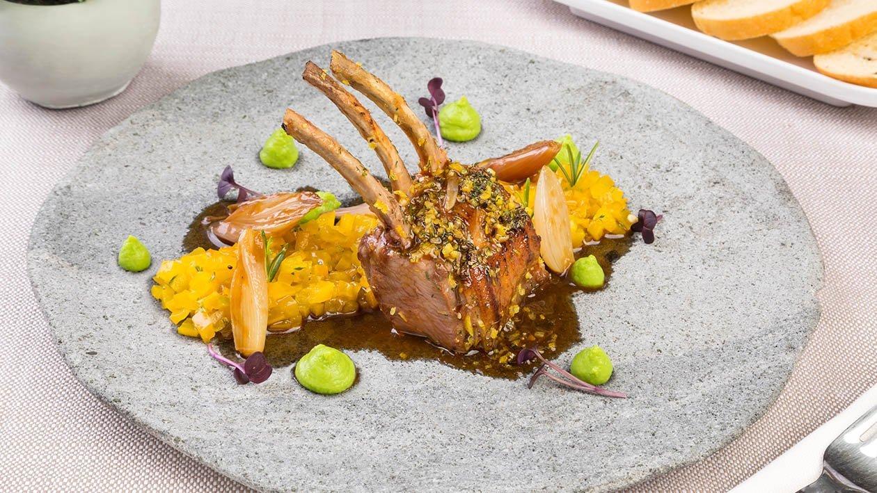 French rack di agnello in crosta di limone, con salsa al brandy, scalogni arrostiti, tartare di peperone giallo e mousse di piselli – Ricetta