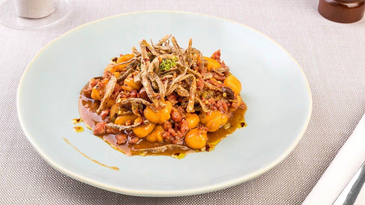 Gnocchetti di patate con ragù di capretto, funghetti chiodini, fiammiferi di cardi croccanti ed olio di peperone crusco – Ricetta