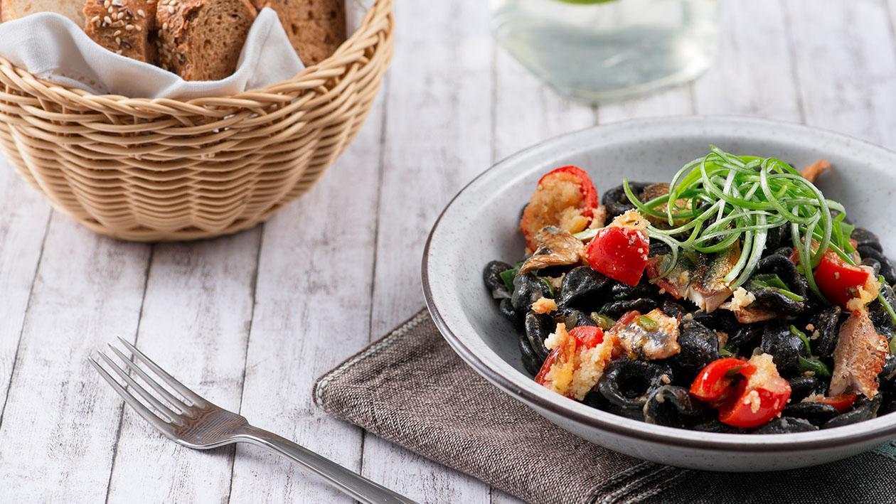 Orecchiette al nero con aringa affumicata, pomodorino gratinato e cipollotti – Ricetta