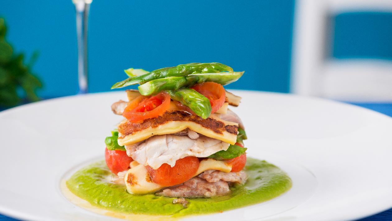 Parmigiana di spigola con pomodoro confit, provola affumicata si crema di asparagi e chips di carote – Ricetta