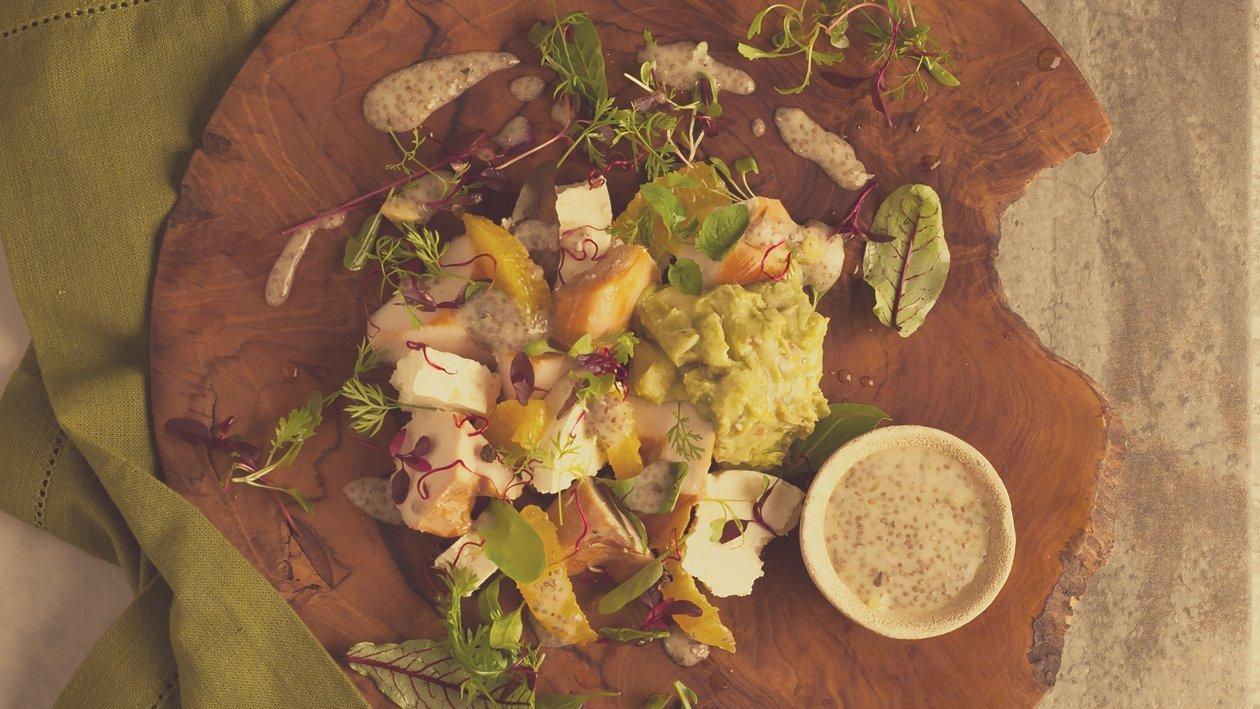 Salade van gerookte kip, feta en guacamole met dressing van sinaasappel en chiazaadjes