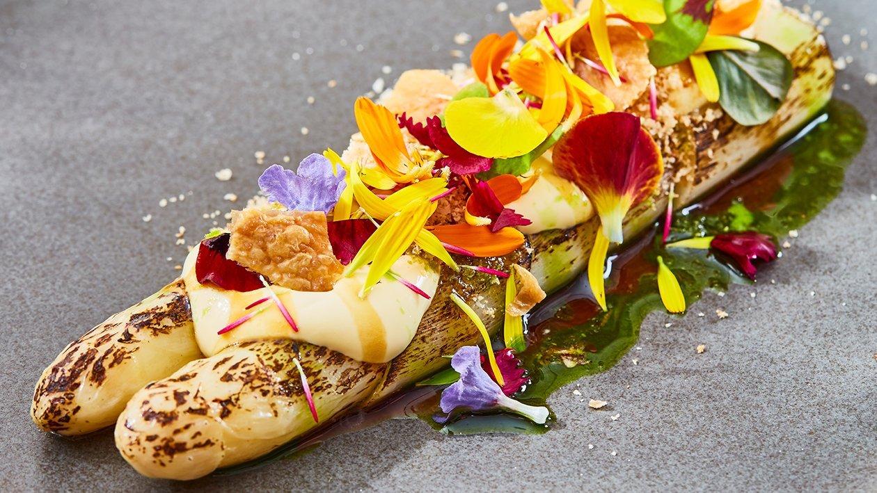 Gebrande asperges met Hollandaise, hazelnoot, gevogelteglace, eidooier, bloemetjes