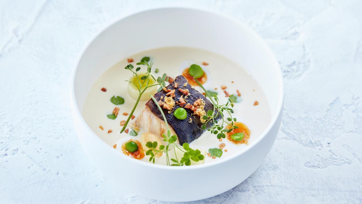Gerookte kabeljauw met een soep van aardappelen en ui geserveerd met doperwtjes en kwarteleitjes