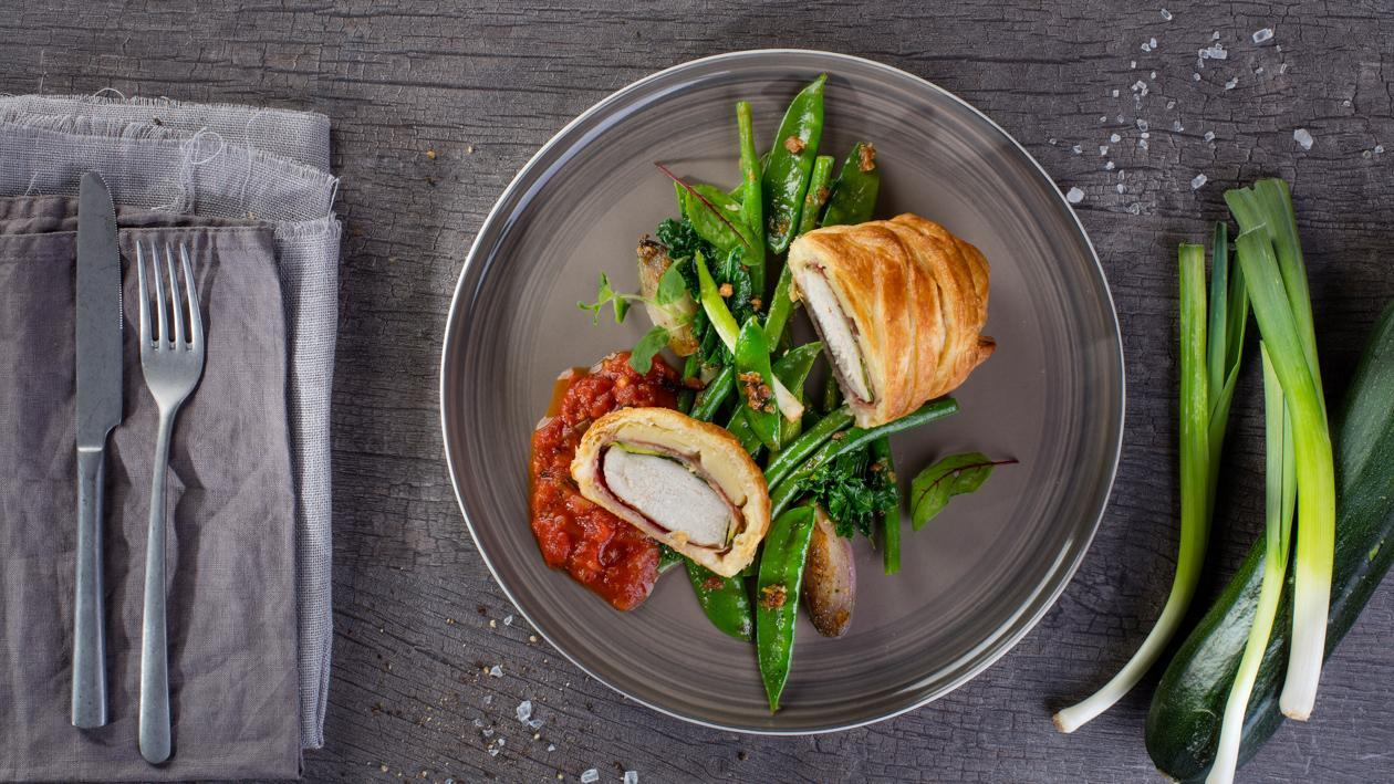 Kurczak w cieście francuskim z pikantnym sosem pomidorowo-paprykowym i glazurowanymi zielonymi warzywami
